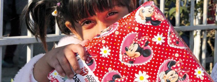Banner dell'iniziativa Azione Pacchetto Regalo con bimba felice con un pacchetto in mano